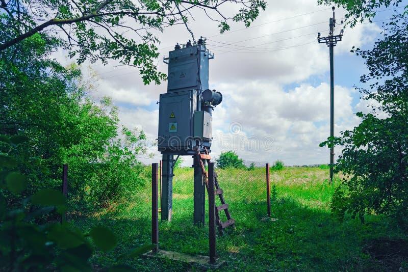 Alter arbeitender ländlicher Transformator der elektrischen Verteilung am Waldsonnigen Tag, das Konzept von industriellem lizenzfreie stockbilder