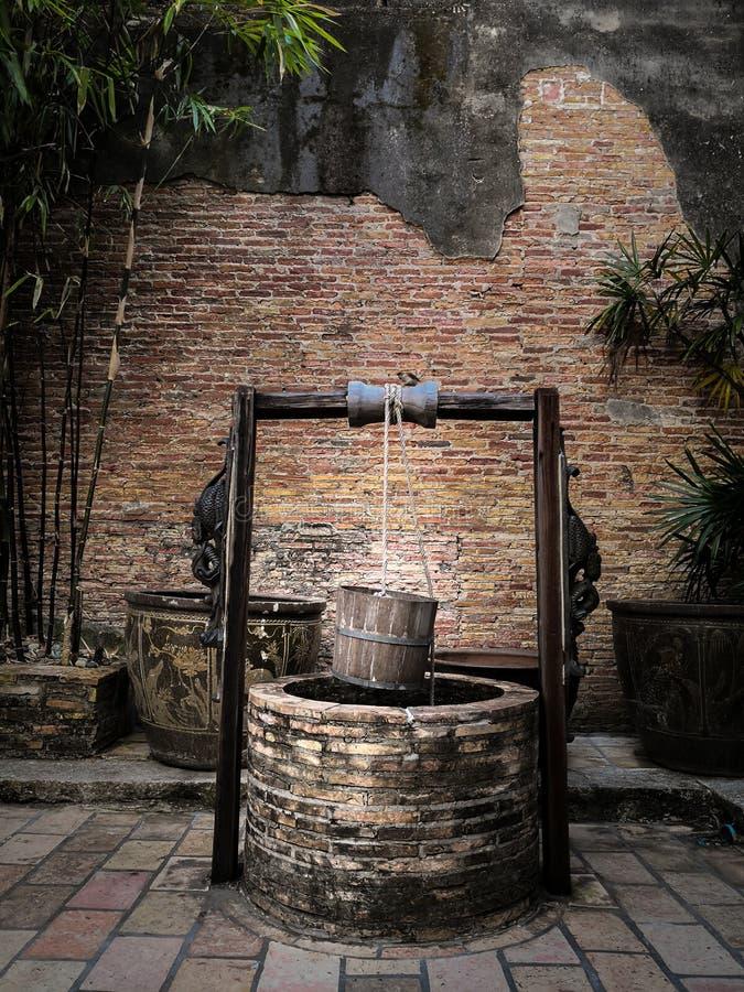 Alter artesischer Brunnen mit hängendem hölzernem Eimer und hölzernem Dach lizenzfreie stockfotografie