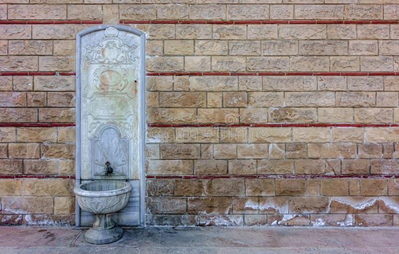 Alter, aufwändiger, prägeartiger weißer Marmorbrunnen auf einer historischen Wand stockfotografie