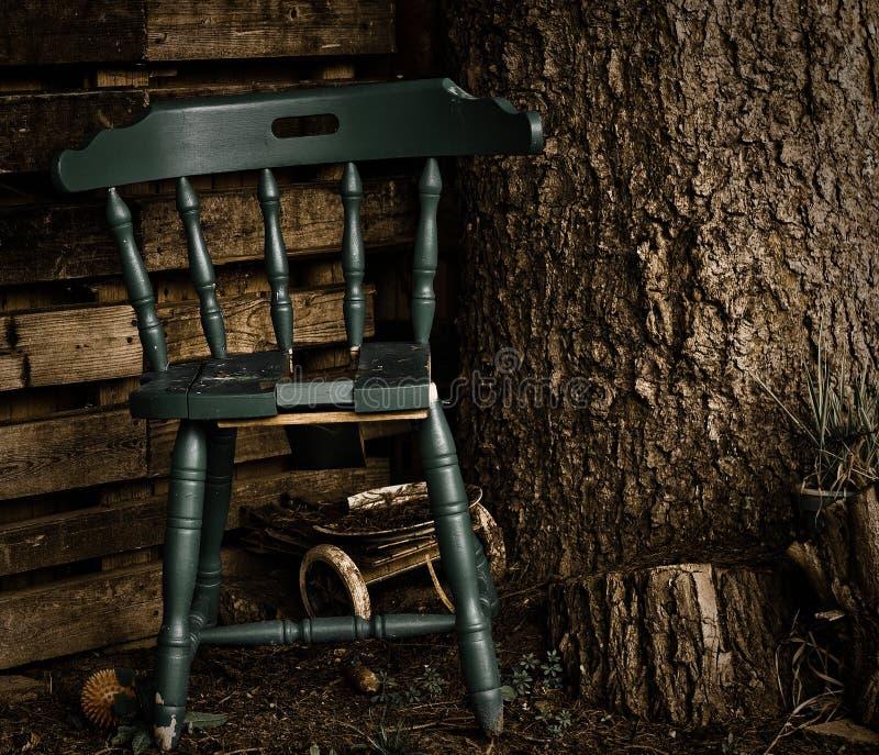 Alter blau-hölzerner Stuhl in einer ruhigen Ecke, unter einer Kiefer stockfotografie