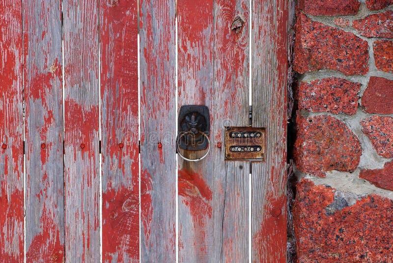 Alter brauner Türgriff und Kombinationsschloß auf hölzerner grauer roter Tür und menschlichen Zaunbrettern lizenzfreies stockfoto