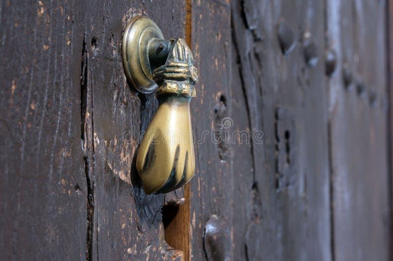 Alter Bronzetürgriff in Form einer Hand Brown-Holztür eines Hauses in der spanischen Stadt von Ronda stockbild