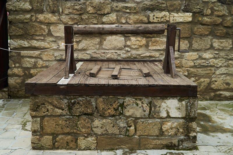 Alter Brunnen im Hof des mittelalterlichen Schlosses mit Backsteinmauer stockfoto