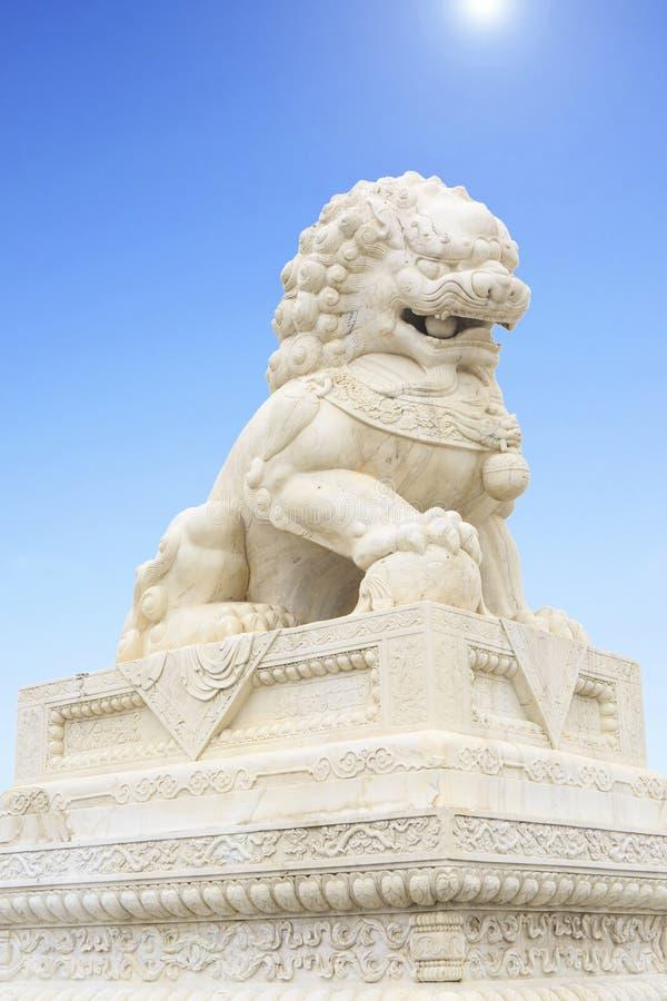 Alter chinesischer Steinlöwe, chinesischer Wächterlöwe mit chinesischer Trachtenmode lizenzfreie stockfotos