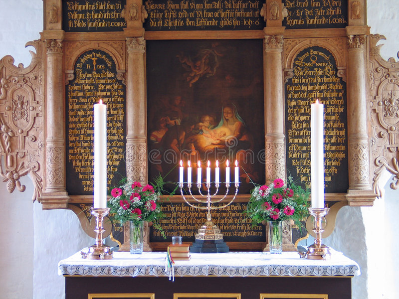 Alter in a church. With candles and flowers during Baptismal ceremony stock image