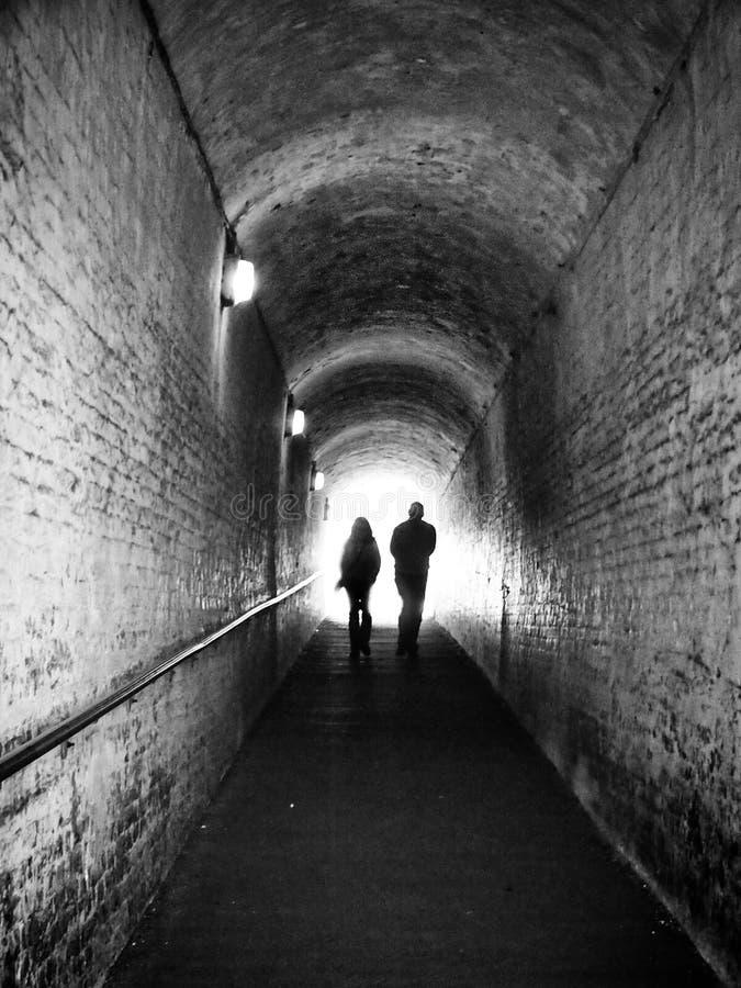 Alter dunkler Fußgängertunnel mit zwei unrecognisable Leuten im Schattenbild gegen weißes Licht vorwärts gehend stockfotos