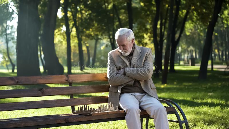 Alter durchdachter Mann, der Schach im Park allein, Sozialversicherung f lizenzfreies stockfoto