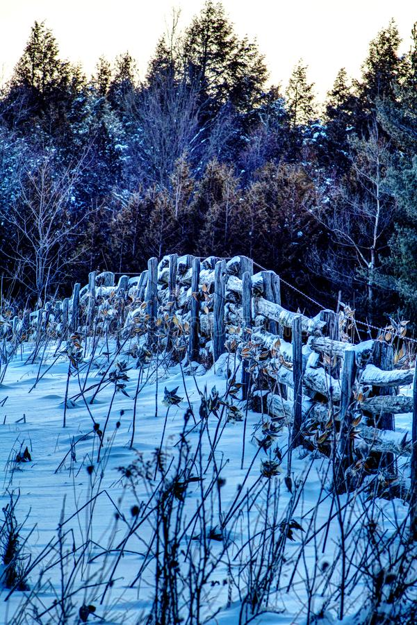Alter durchgesetzte Forderung Bauernhof-Zaun-In A Schnee im frühen Licht lizenzfreies stockfoto