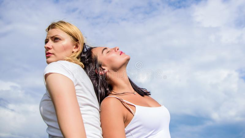 Alter ego concept. Blonde and brunette back to back. Concentrated and relaxed. Friend you trust. Friendship and trust stock photos