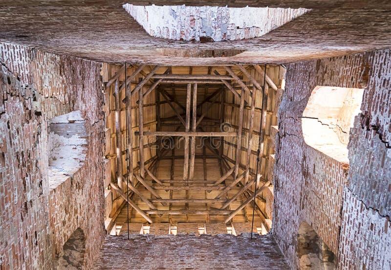 Alter Einsturzturmziegelstein mit Bogenfenstern, Perspektive von unterhalb des aufwärts hölzernen Dachs, mystischer Weg durch ver stockfotos