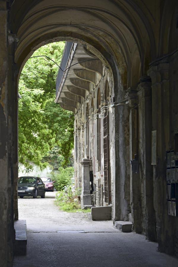 Alter europäischer Hof mit hölzernen Balkonen Ansicht durch einen Steinbogen, zum von Bäumen zu grünen Abweichen vom Yard Budapes lizenzfreie stockfotografie