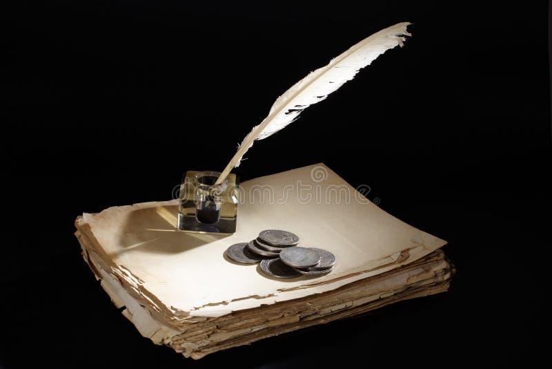 Alter Füllfederhalter des Tintenfasses und Silbermünzen der Papiere, auf einem schwarzen Hintergrund lizenzfreie stockfotos
