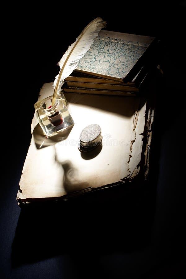 Alter Füllfederhalter des Tintenfasses und Silbermünzen der Papiere, auf einem schwarzen Hintergrund stockfoto