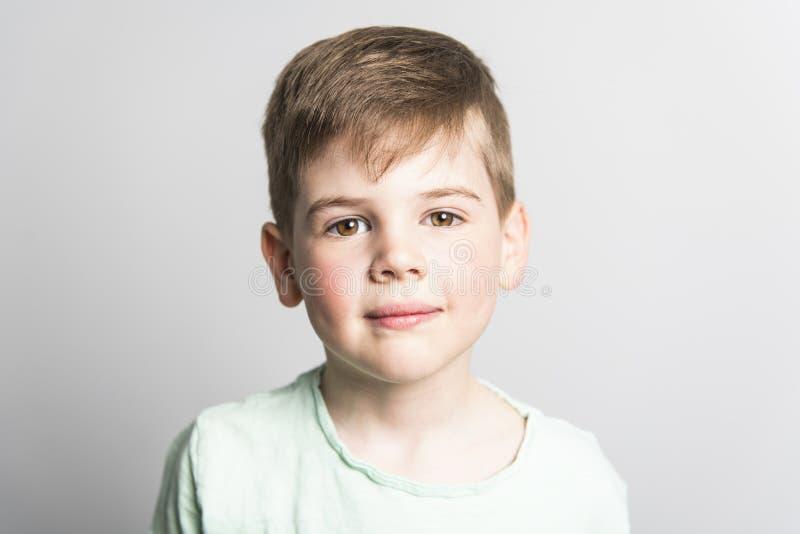 Alter Fünfjahresjunge, der über weißem Studiohintergrund aufwirft lizenzfreies stockfoto