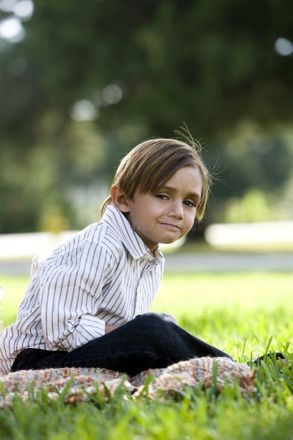 Alter Fünfjahresjunge, der auf Decke im Park sitzt stockfoto