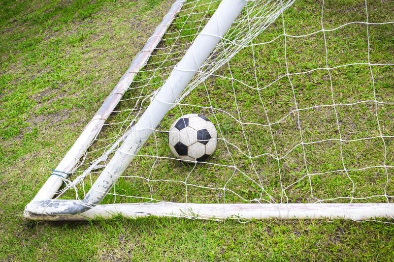 Alter Fußball im alten Zielnetz stockbild