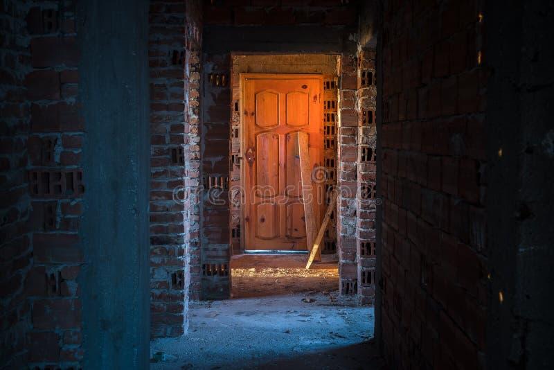 Alter, furchtsamer, verlassener Hausinnenraum Holztür am Ende des furchtsamen konkreten Korridors Architekturstruktur lizenzfreie stockfotografie