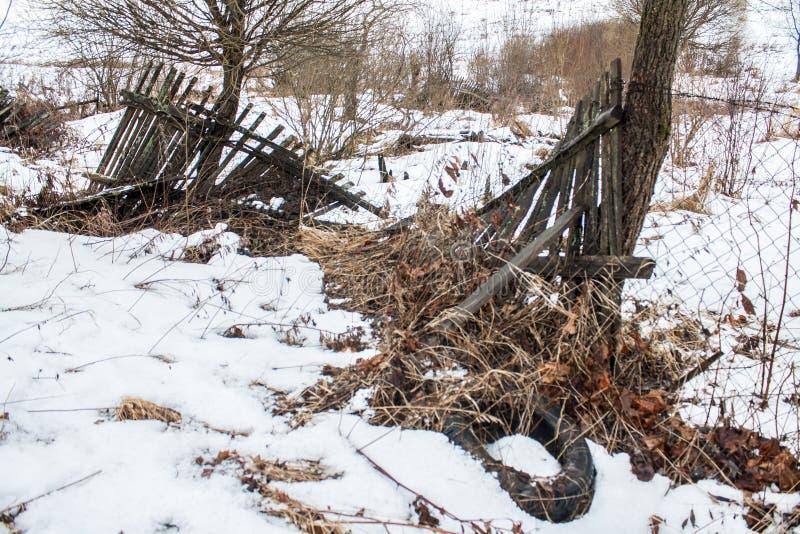 Alter gebrochener Zaun mit einem alten Reifen lizenzfreies stockfoto