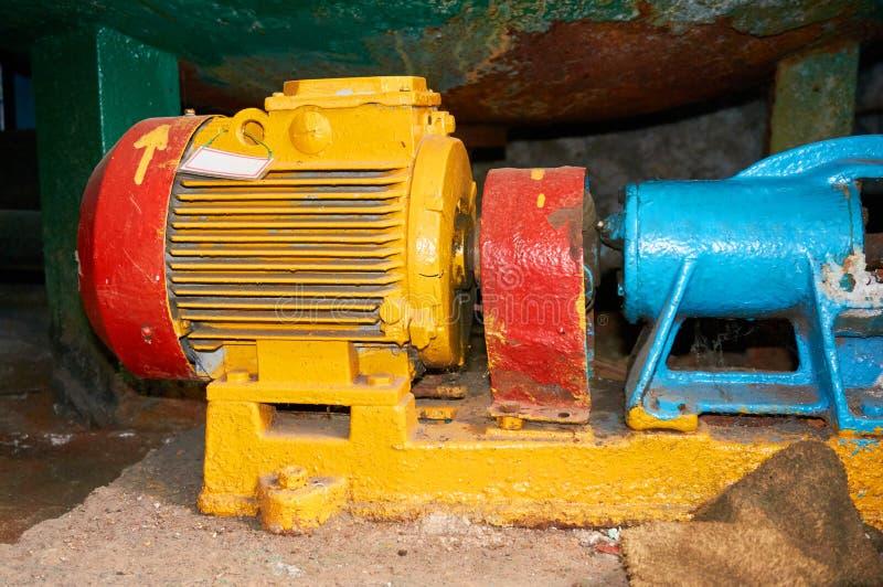 Alter gelber Elektromotor mit einer blauen Pumpe angeschlossen lizenzfreie stockbilder