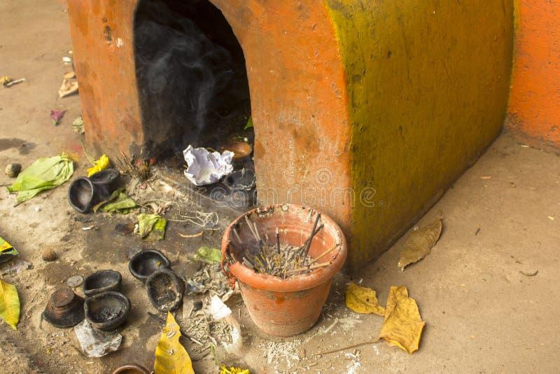 Alter gelber schäbiger hindischer Tempel mit Angeboten und rauchenden Räucherstäbchen stockbilder