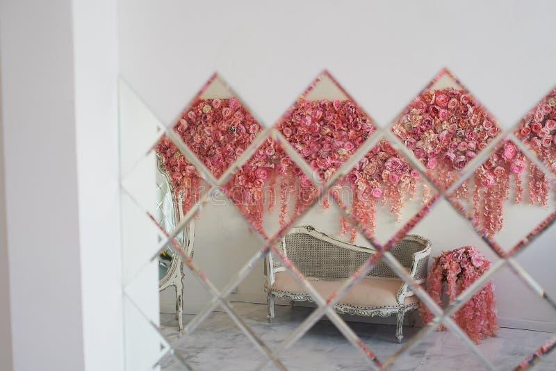 Alter geschnitzter Daybed mit weicher Polsterung gegen eine weiße Wand verziert mit rosa Blumen Herrliche Girlande Der Innenraum lizenzfreies stockbild