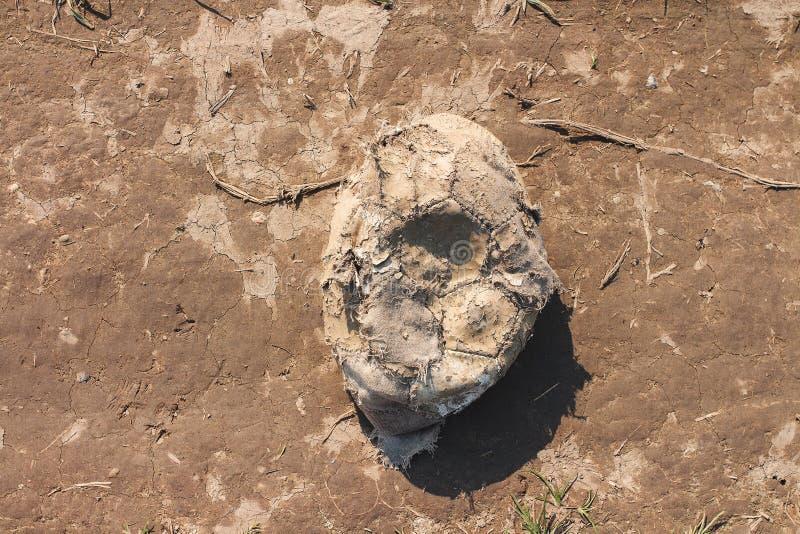 Alter getragener entlüfteter Fußballball verlassen im Schmutz lizenzfreies stockbild