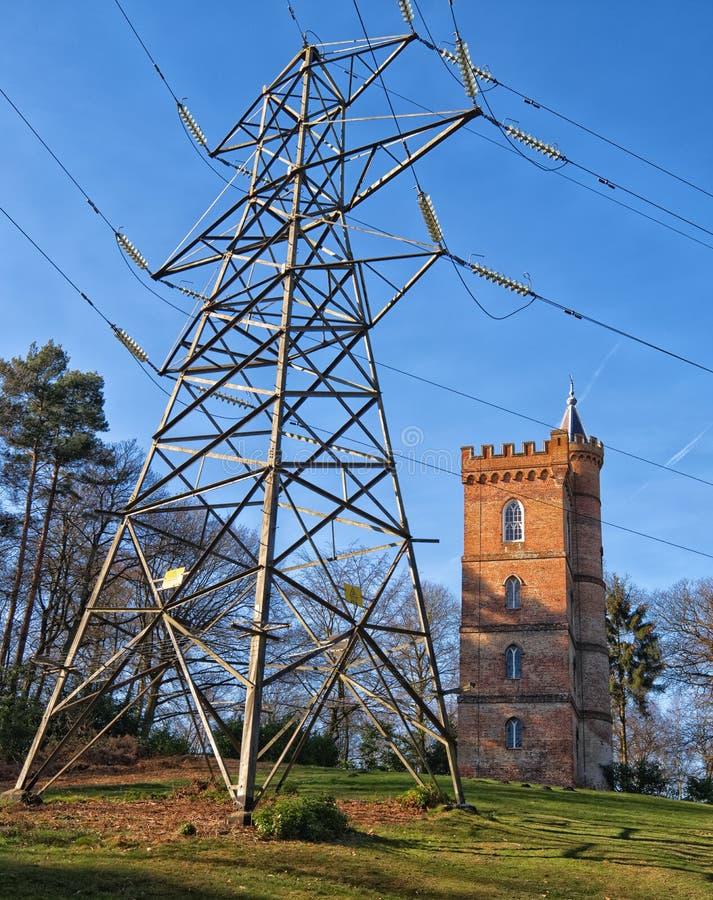 Alter gotischer Turm sitzt hinter modernem Strommast lizenzfreie stockfotos