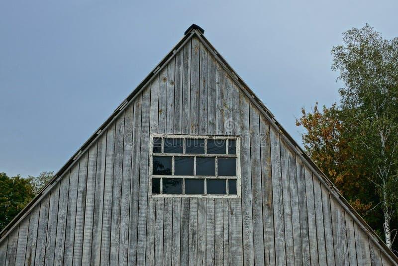 Alter grauer hölzerner Dachboden mit Fenster auf dem Himmelhintergrund lizenzfreie stockfotos