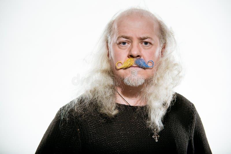 Alter grauhaariger Mann mit einem farbigen Schnurrbartmagier und -zauberer stockfotografie