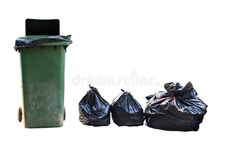 Alter großer grüner Radbehälter und Stapel von vollen Abfalltaschen lizenzfreie stockfotografie