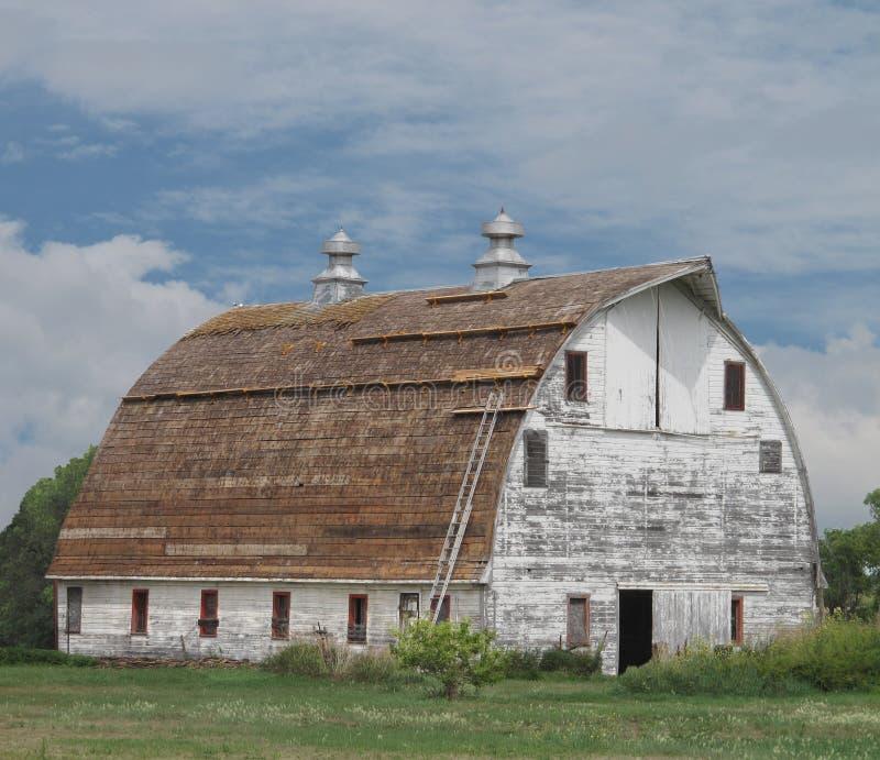 Alter großer weißer hölzerner Stall mit gebogenem Dach. lizenzfreies stockfoto