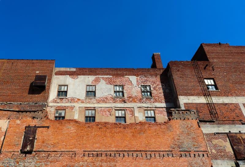 Alter grungy Backsteinbau, der teilweise heruntergerissen worden ist und aber umgebaut wird, noch sehr rau ist stockbilder