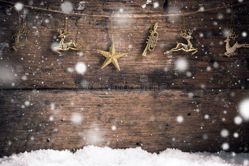 Alter hölzerner Beschaffenheitsgoldstern, Goldren und Dekoration mit Schneeflocken-Weihnachtshintergrund stockbild