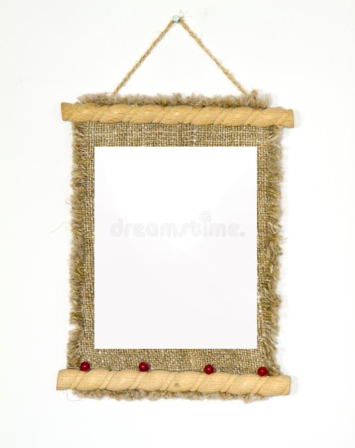 Alter hölzerner Bilderrahmen, der an einem Seil lokalisiert auf weißem BAC hängt lizenzfreies stockfoto