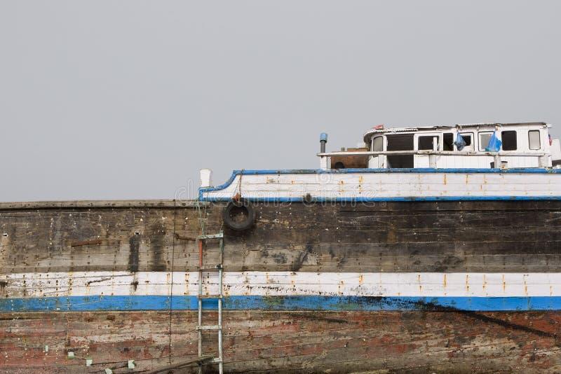 Alter hölzerner Dhow Khor Fakkan UAE wusch sich oben auf Ufer vor Khor Fakkport stockfoto