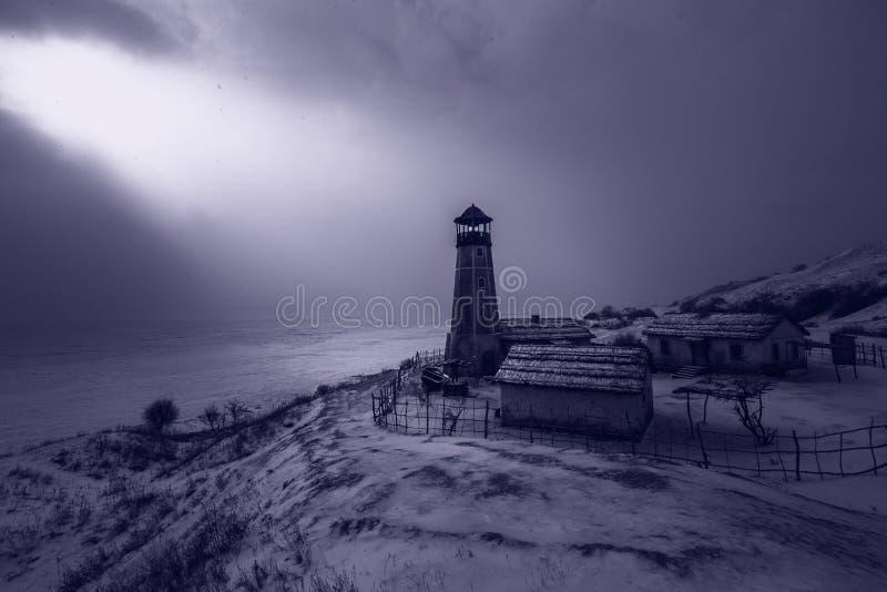Alter hölzerner Leuchtturm in der Nacht am Rand des gefrorenen Hafens mit bewölktem Himmel Blaues atmosphärisches Licht stockbild