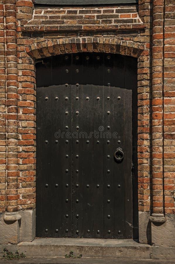 Alter hölzerner Zugang auf gotischer Kirche in der Gasse von Brügge stockfoto