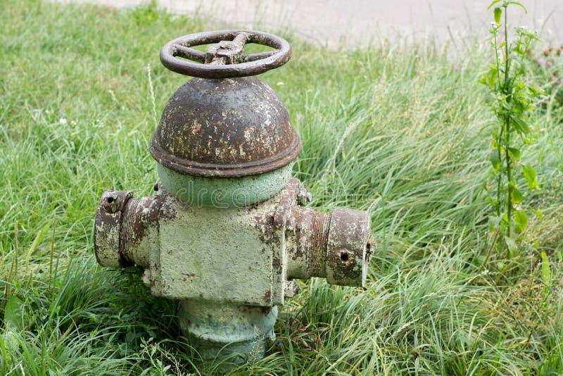 Alter Hydrant auf einem Hintergrund des grünen Grases stockfotografie