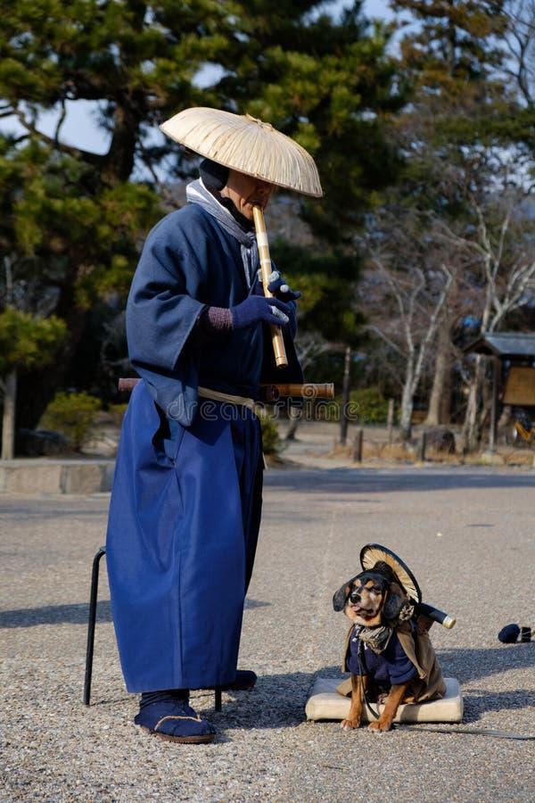 Alter japanischer Mann mit seinem Hund, der die Flöte spielt, kleidete im traditionellen blauen Kostüm und im Tragen eines Hutes  lizenzfreie stockfotos