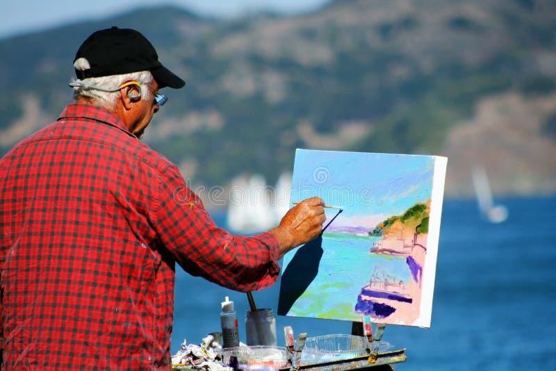Alter Künstler, der ein schönes Landschaftssegeltuch malt lizenzfreie stockfotos