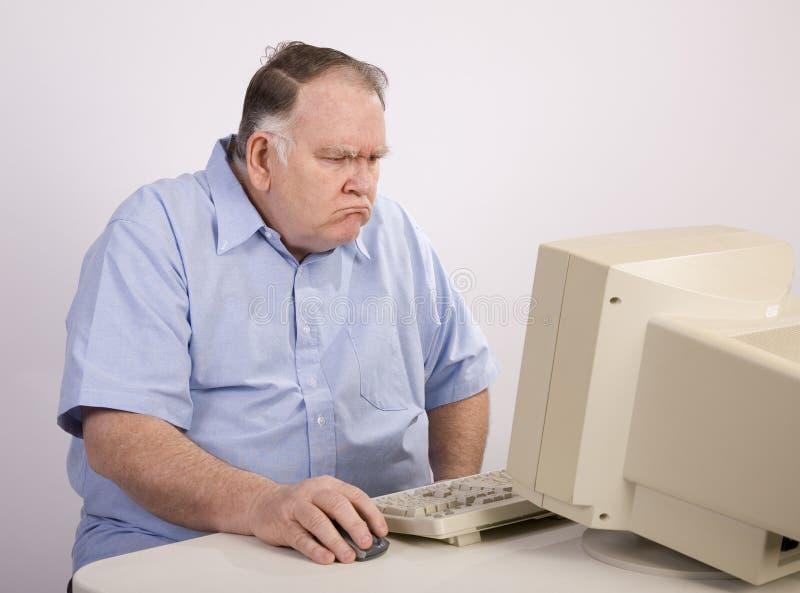 Alter Kerl am Computer und mürrisch stockbilder