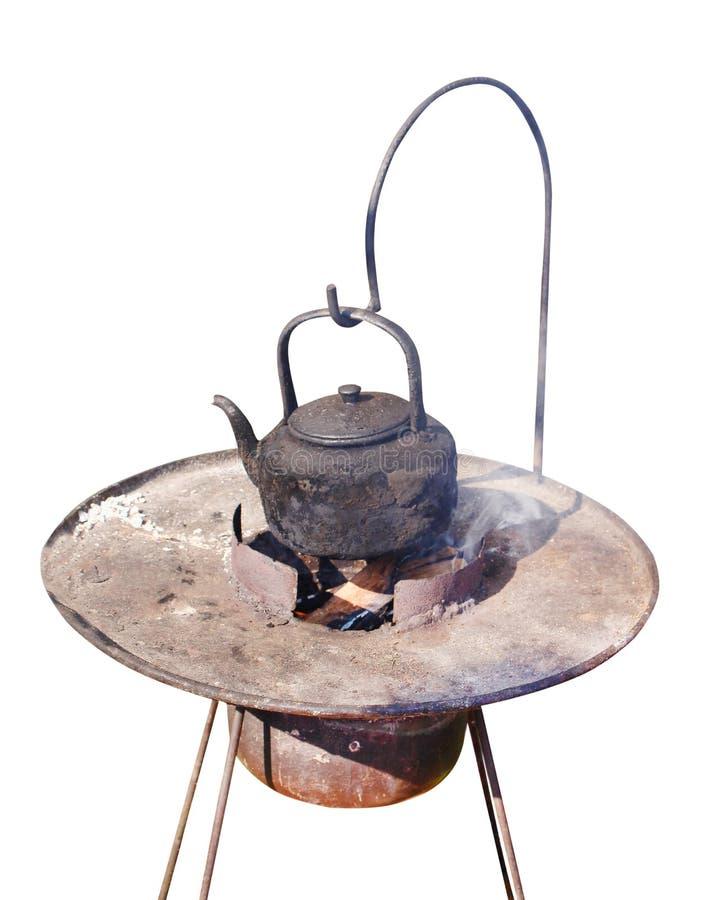 Alter Kessel des schwarzen Tees mit Wasser, das am alten Stahlholzkohlenofenim freien lokalisiert auf weißen Hintergrund und dem  stockfotos