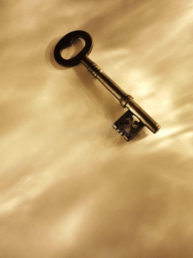Alter Kirchen-Schlüssel auf einem Papierhintergrund mit Goldbeleuchtung stockfoto