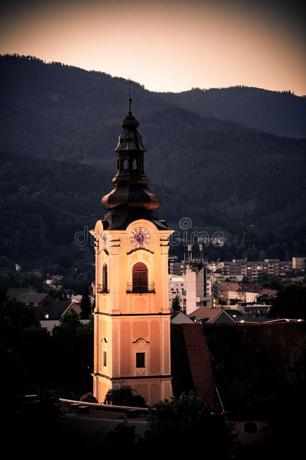 Alter Kirchturm mit einer Uhr vor einer österreichischen Stadt bei Sonnenuntergang lizenzfreies stockbild