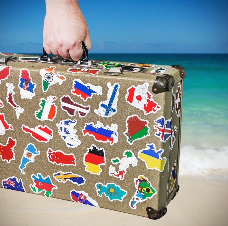 Alter Koffer mit Aufklebern von Flaggen von des Reisens lizenzfreie stockbilder