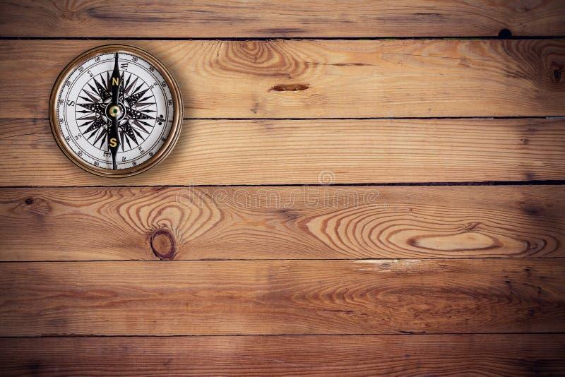 Alter Kompass auf hölzernem Hintergrund und Beschaffenheit lizenzfreie stockfotografie