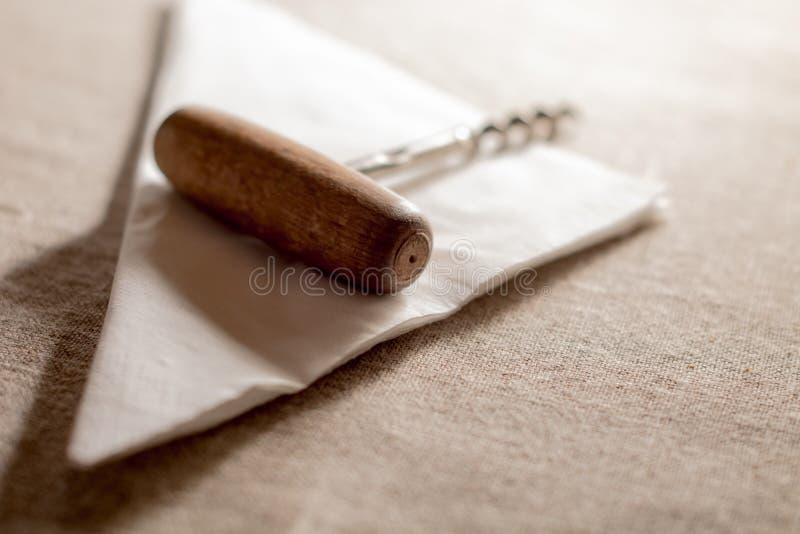 Alter Korkenzieher auf einer weißen Serviette lizenzfreies stockbild