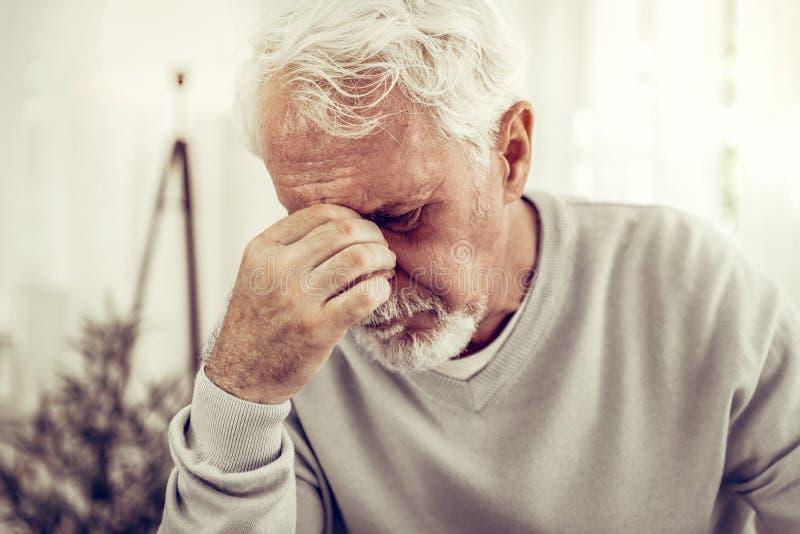 Alter kranker grau-haariger Mann in der beige Strickjacke, die den schrecklichen Schmerz glaubt lizenzfreies stockbild