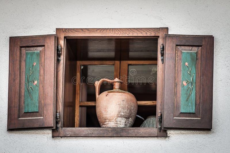 Alter Krug, der im weit offenen hölzernen Fenster steht stockbild