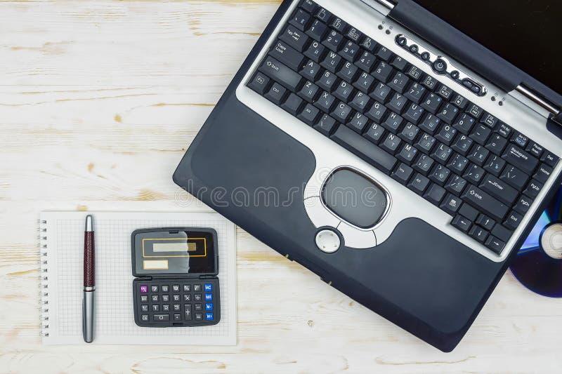 Alter Laptop mit Laserscheibe, einem Taschenrechner, einem Notizbuch und einem Stift auf a lizenzfreies stockbild